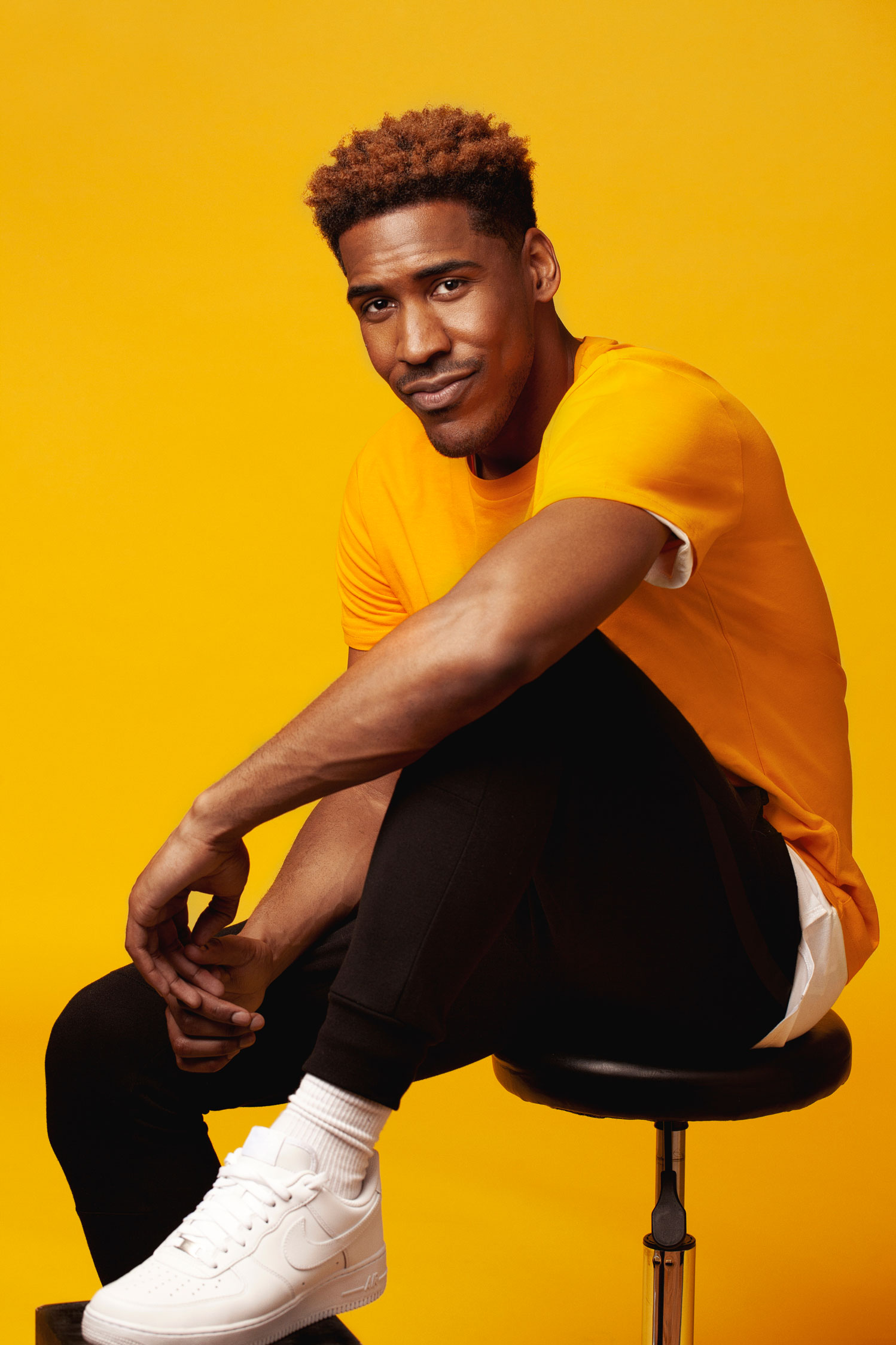 Photo portrait of a singer sitting in front of a yellow backdrop. Portrait media commercial lifestyle for artist.
