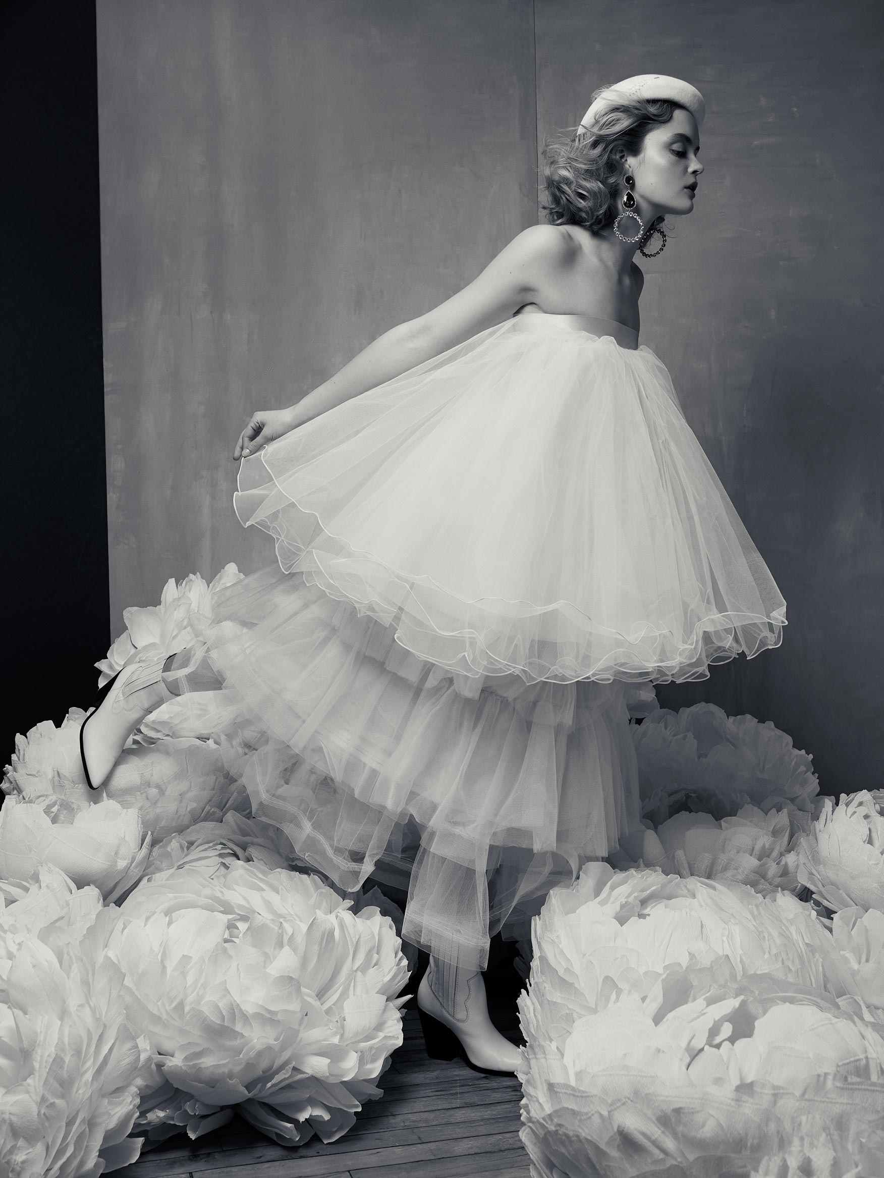 Photo portrait noir et blanc en studio d'une robe en tule et des fleurs géantes