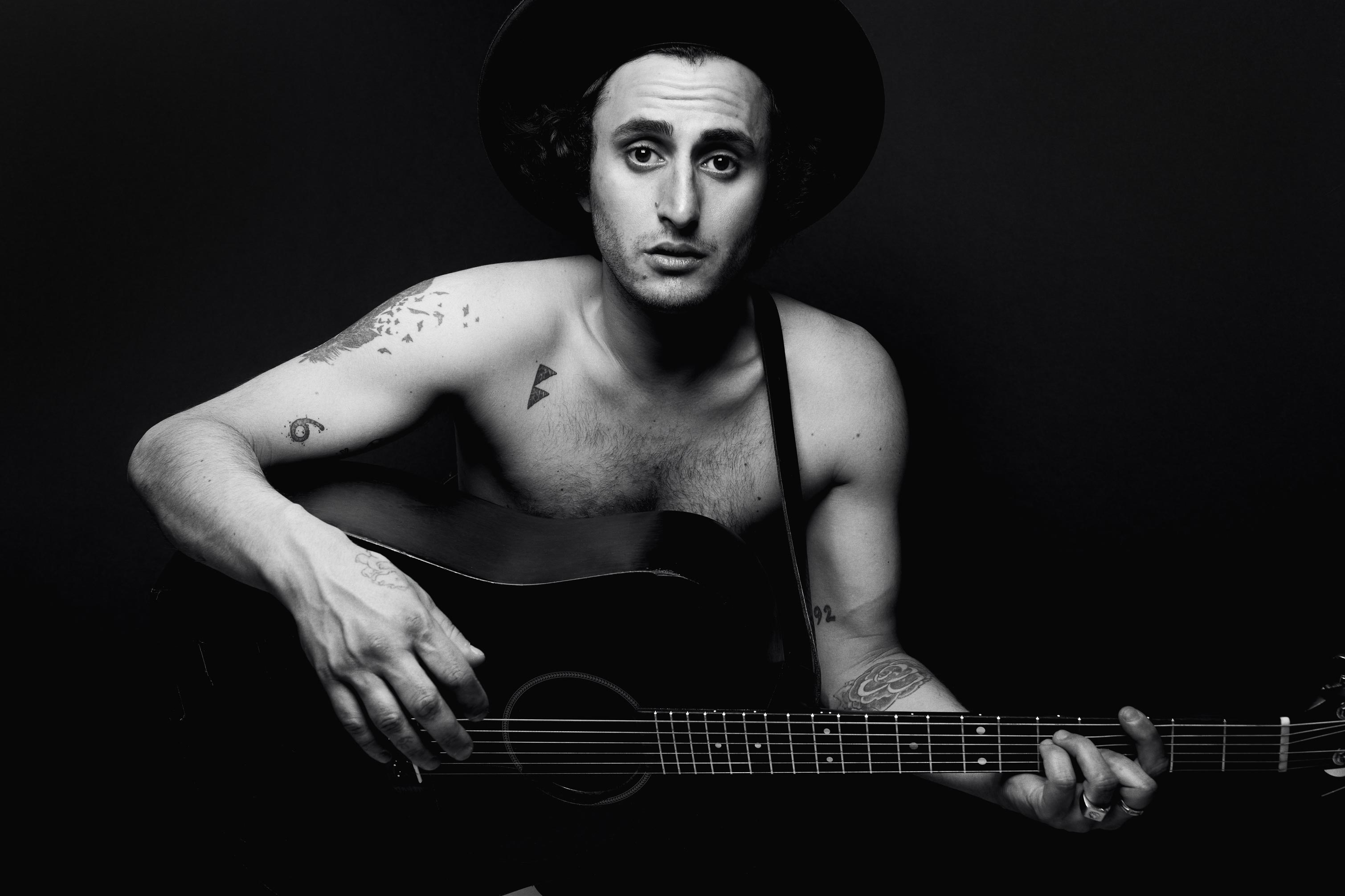 Portrait photography of Rick Pagano in chest with his guitar on a black background. Music album photographer in Montreal.