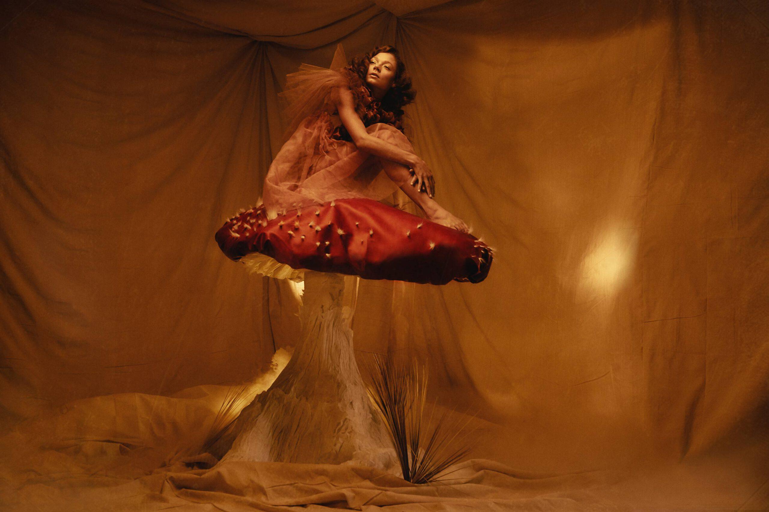 Dariane Sanche Photographe professionnelle spécialisée en photo editorial mode et creative. Photo d'une femme assise sur un champignon géant avec de la fumé au sol.