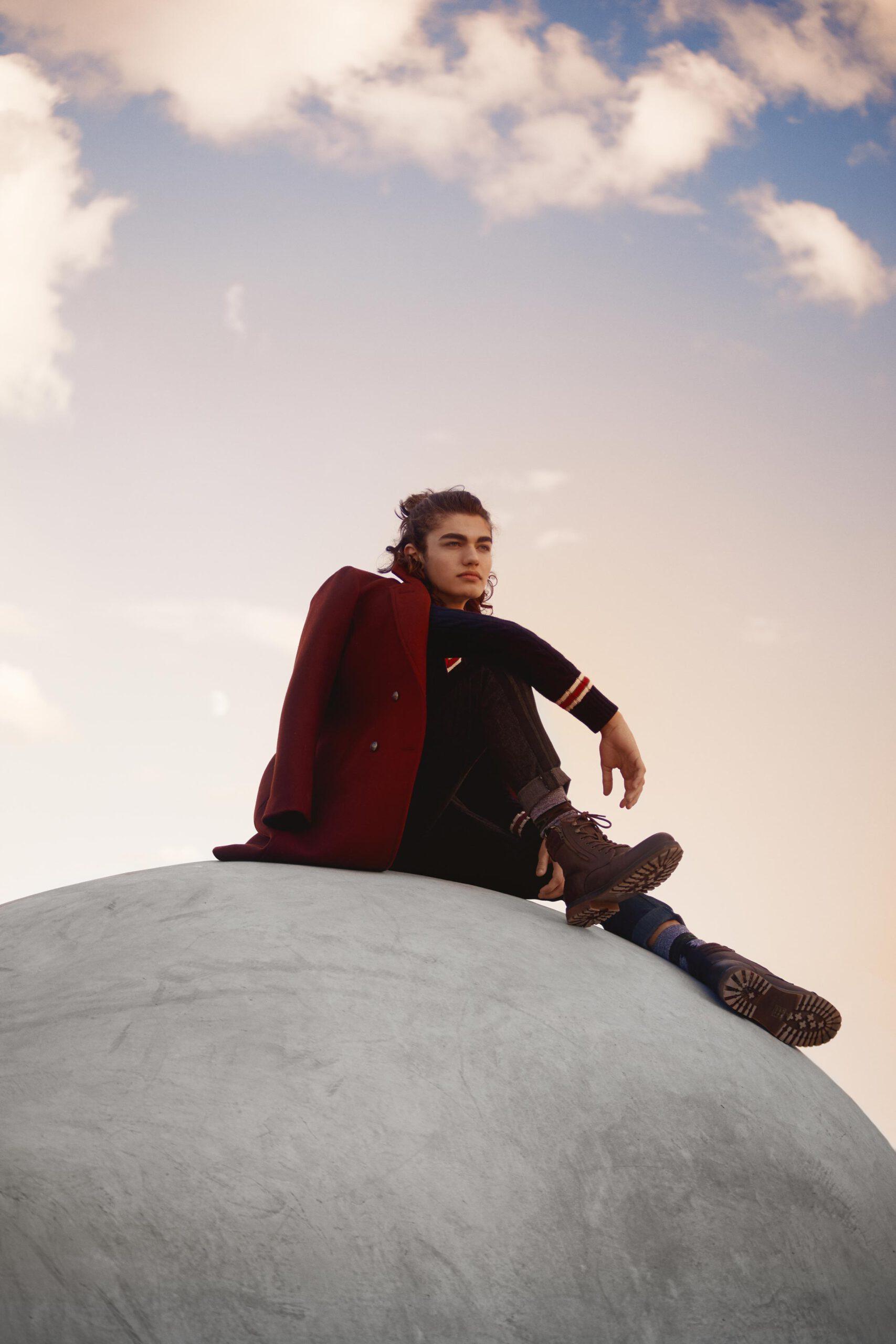 Portrait photographie d'un jeune homme de 20 ans assis sur une boule en ciment beton.