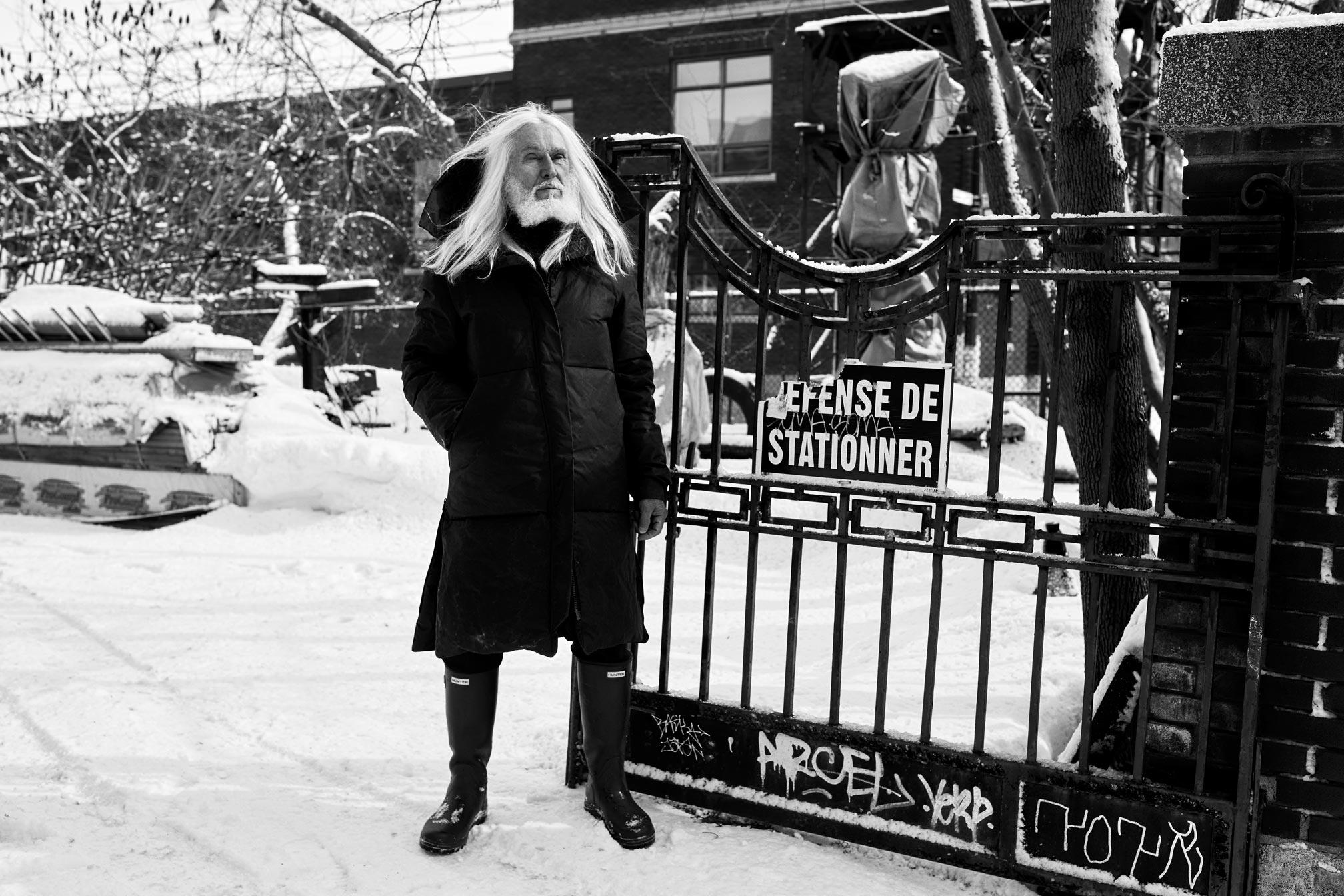 Photo portrait noir et blanc du sculpteur Armand Vaillancourt devant sa résidence de Montreal.