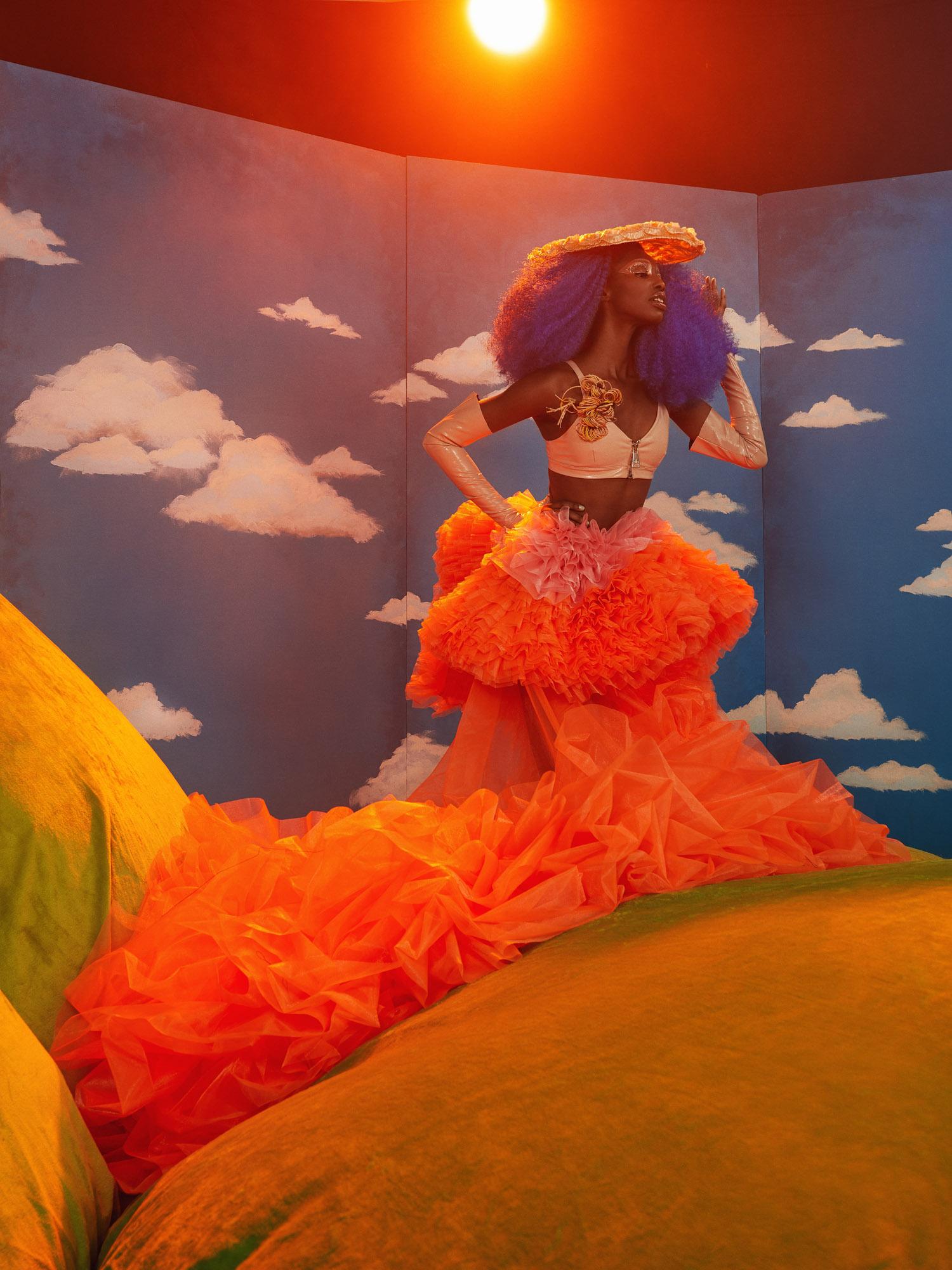 Fashion model wearing big orange tule dress on grass hill at sunset